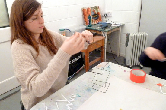 Making vertical sculptures: student working up from the base