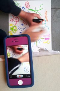 Playing a game of association with drawing, documented on a mobile phone with photo burst app