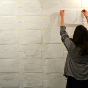 Libby placing her minimalised drawings on the wall as she completes them