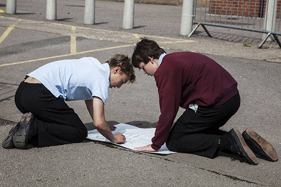 Boys enthusiastically draw using graphite sticks to create textured rubbings