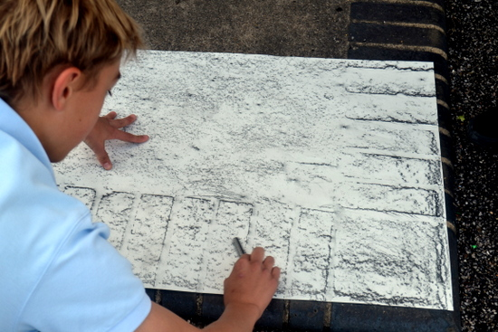 Boy explores drawing with graphite by making rubbings of the school yard