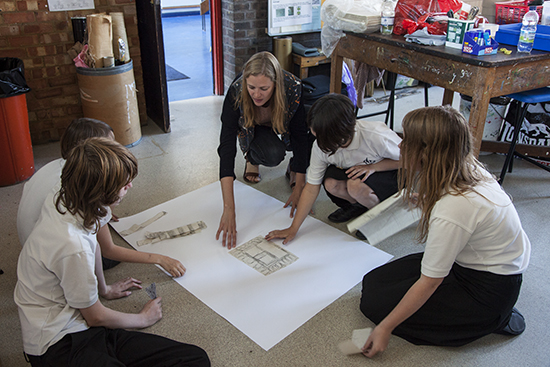 Anne works with students describing how they should collage elements together to create a new building or image