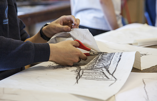 Drawing being cut to incorporate into a collage created by a group of five students working together