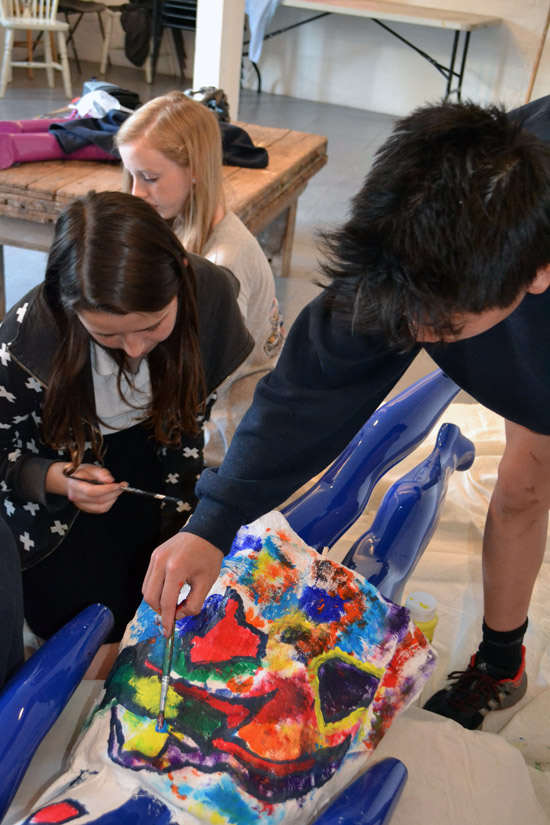 Students paint the back of a model