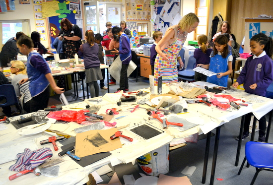 Busy classroom with three activities: exploring paint, printmaking and making rubbings