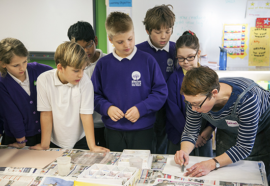 Artist Rachael Causer demonstrates to year five pupils at Ridgefield how to make a rubbing with graphite