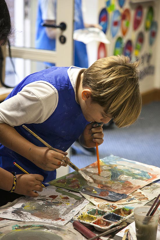 Pupil explores mark making by blowing paint across the paper with a straw