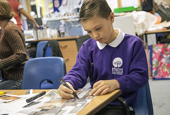 Pupil traces over his collage in acetate with a permanent marker