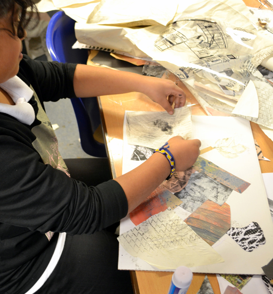 Pupil uses textured paper created in the morning session to make a back ground for their new building