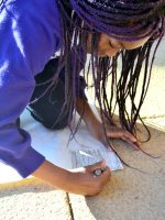 Pupil using a graphite stick to take a textured rubbing outside her classroom