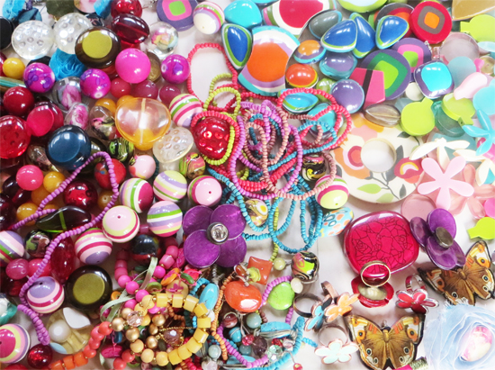 Packed full of mixed jewellery/beads in glorious colours. The box includes translucent resin and opaque acrylic beads of all sizes and shapes, plus a selection of bright mixed earrings, rings and smaller pieces of jewellery for textural variety and richness. Box measures 13cm x 13cm x 18cm.