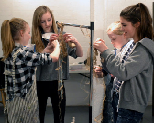 Two groups of students work with string, hanging it over a bar to create suspended sculptures