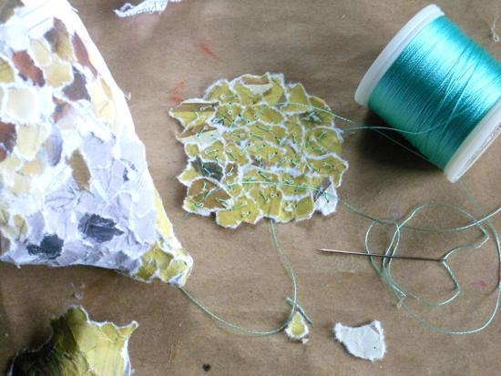 Adding handstitching to collaged segment to glue on to bird's breast