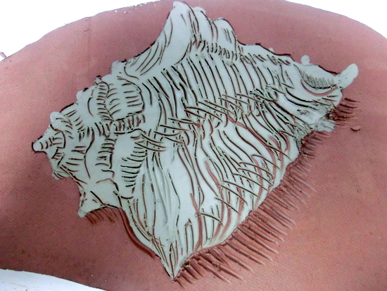 Conch shell scraffito into a coloured clay slip