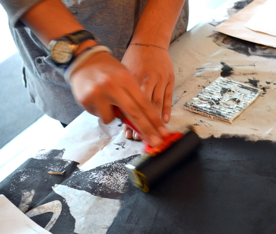 Preparing the roller by rolling and working a thin layer of ink onto acetate