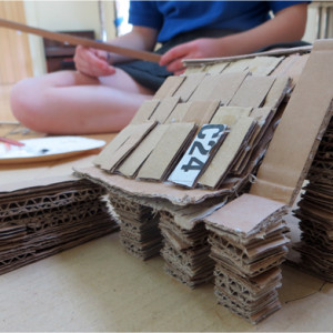 "Transforming an ordinary, everyday material into an extraordinary object. These autobiographical architectural sculptures use corrugated cardboard, laid in strips on their side, to create sculptures designed to be peered in to!  [themify_button style=""xlarge block"" link=""/my-house-a-cardboard-construction-project/"" color=""#78608e"" text=""#ffffff""]Read More[/themify_button]"