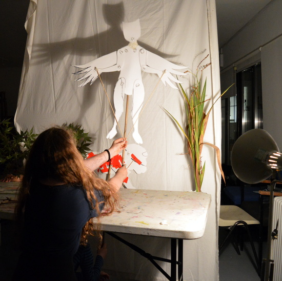 Teenager at AccesArt's Experimental Drawing Class preforming in the shadow puppet play