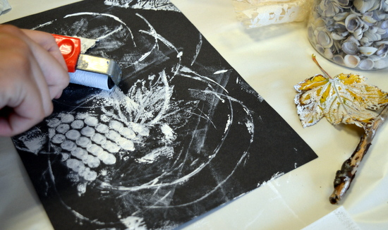 Rolling textures with white block print ink onto a black sheet of cartridge paper