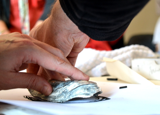 Close up of Andrew drawing around an oyster shell