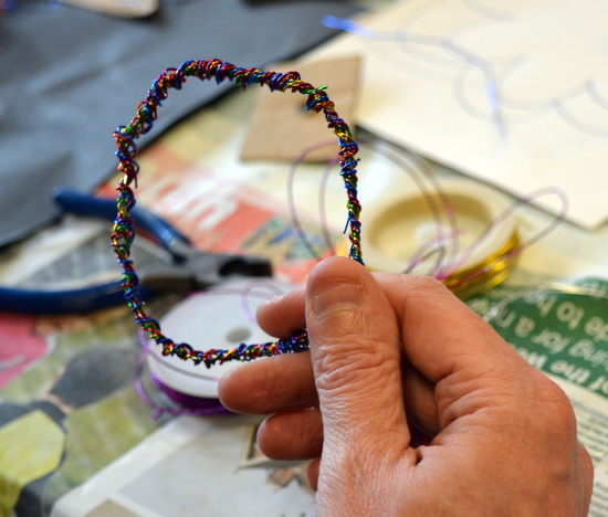 Student works on a wire circle binding coloured wire red2Green_wire