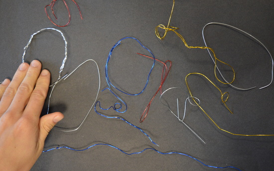 The shift from working in two dimensions to three was quite difficut but here the student enjoys placing flat shapes madein wire onto black paper
