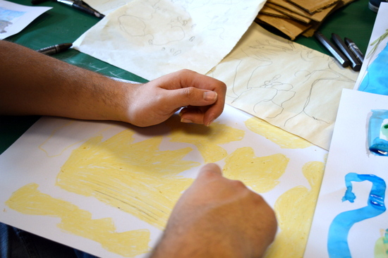 Steve looks at his tracing and draws filled shapes in oil pastel