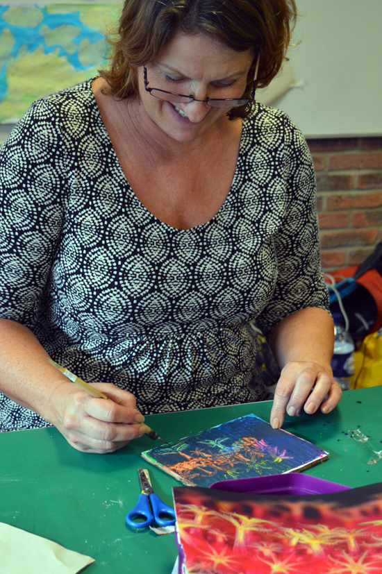 Sally, tutor at Red2Green doing scraffito on a cardboard tablet