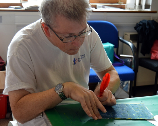 Andrew, learner at Red2Green, uses a feather to scratch into a plate made by rubbing black pastel over a multi-coloured pastel plate