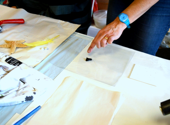 Sheila demonstrates how to 'ink up' a plate by by rolling a thin layer of ink over acetate to distribute it evenly