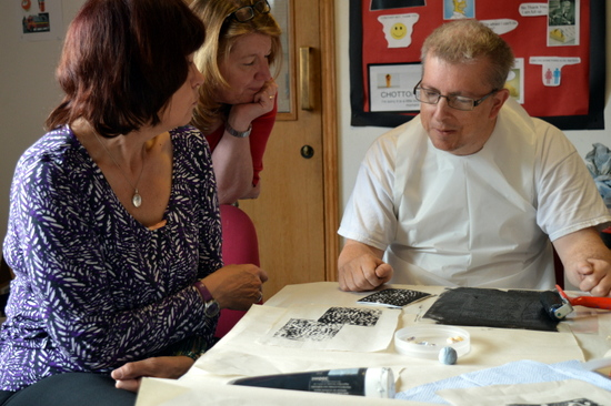Tutor's Jeanette and Sharon at Red2Green look at Andrew's work