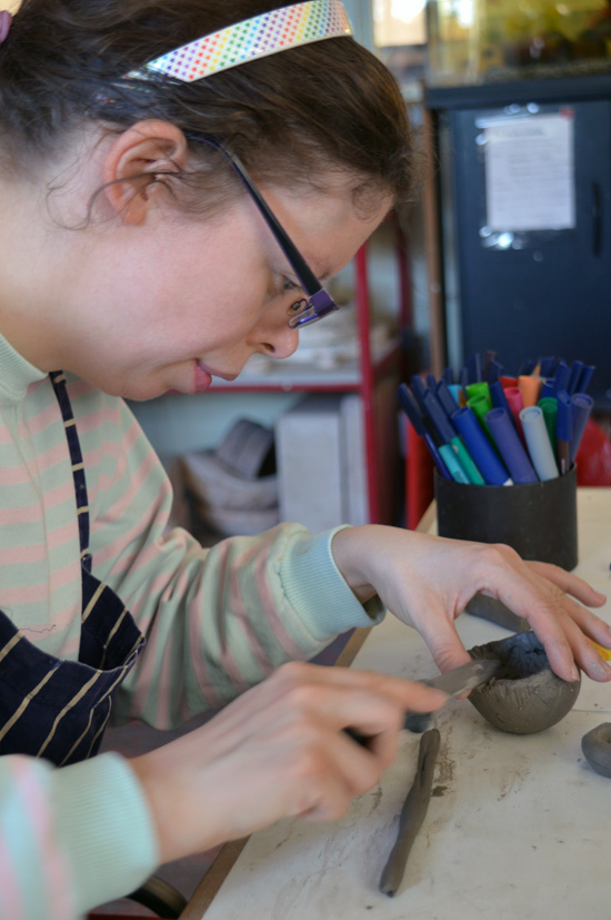 Rosie scores her clay coil before applying the next coil layer and builds up Tweety Pie