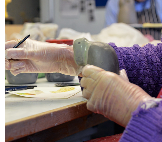 Having smoothed her bird, Jenny paints coloured slip before firing her Robin