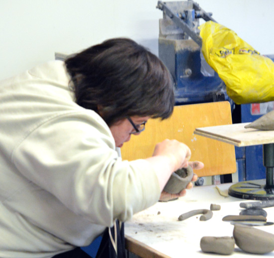 Emma making progress - applying another coil to her emerging clay bird