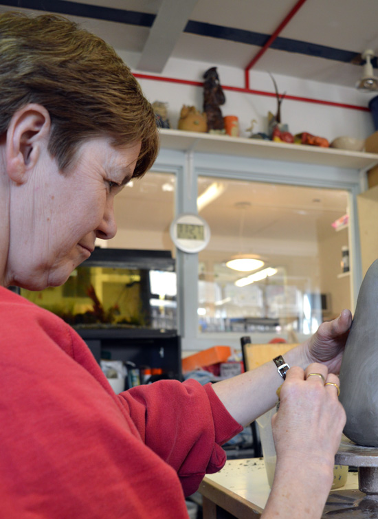Having added the penguin's head, Janette smooths the clay with a wet sponge