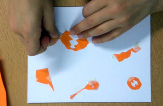 Pupils use small pieces for torn masking tape to stick their shapes down on the board