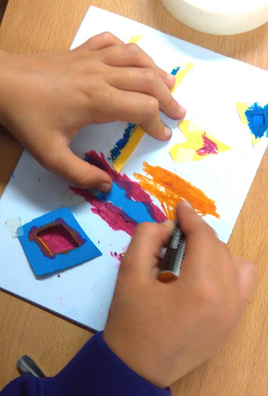 Once the stencils are in place and stuck down, pupils use soft pastels to fill in the gaps around the shapes