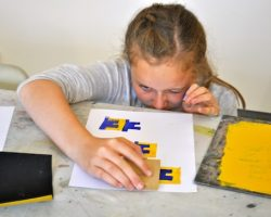 Working with artist Andy McKenzie to create repeat patterns of letters using block printing.