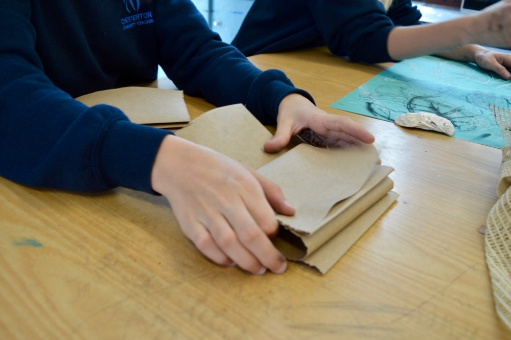 Folding brown paper to create a zigzag sketchbook