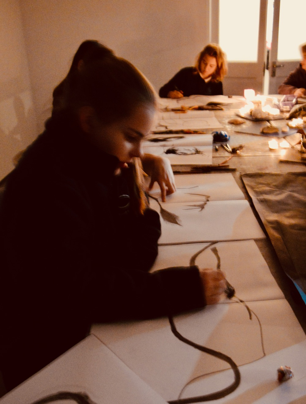 Students working in candlelight - looking for one, strong line