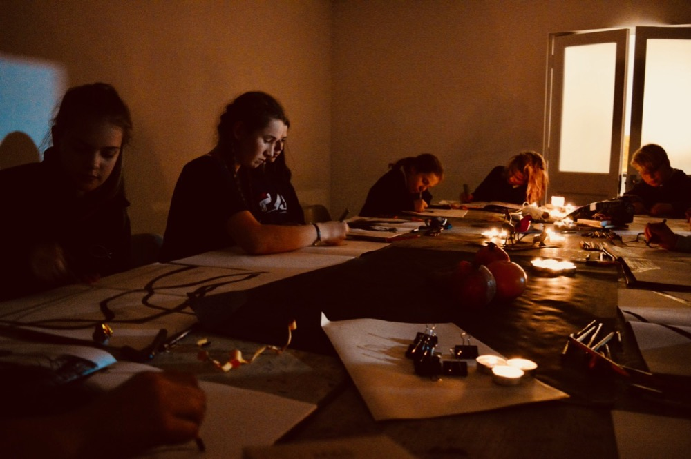 Teenagers working in candlelight at Cambridge ArtWorks - SC