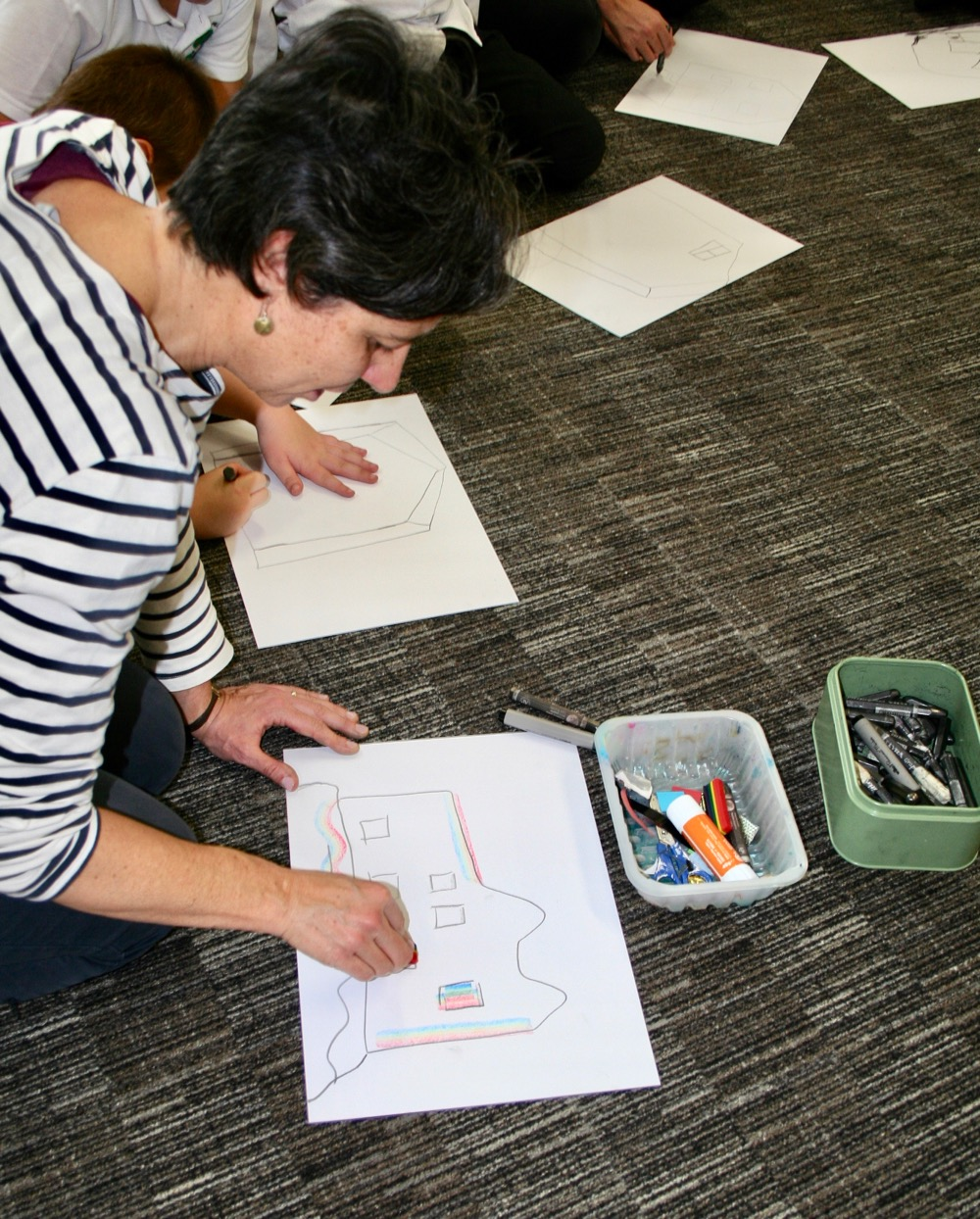 Sheila from AccessArt leading children on a guided drawing exercise using graphite in Mansfield Library