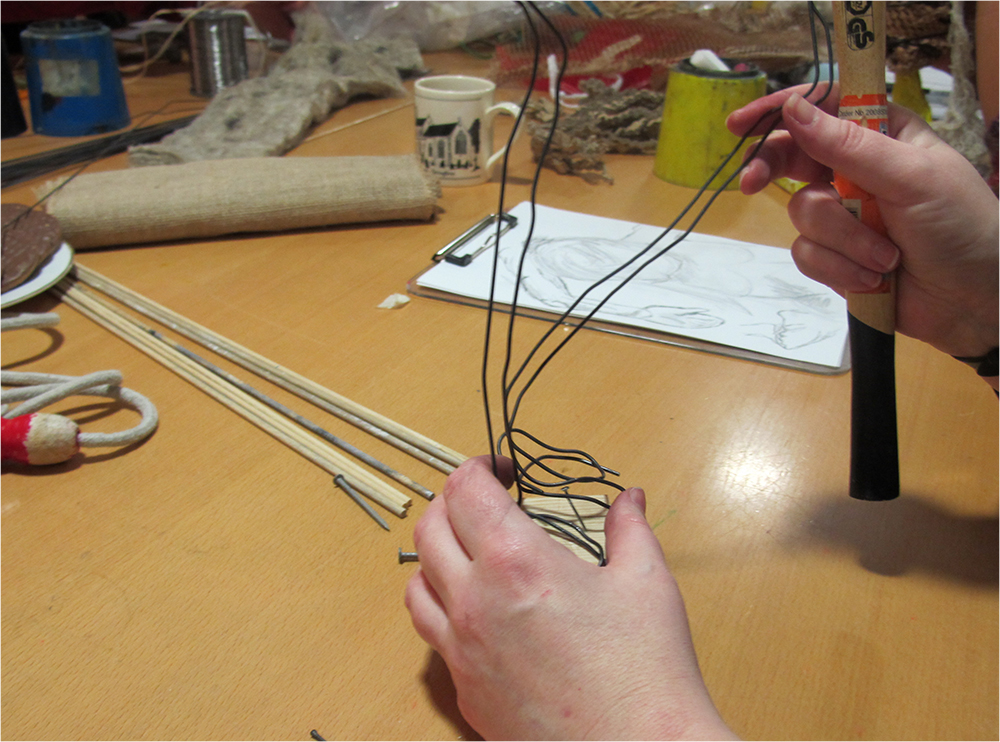 Attaching modelling wire with nail to wooden block to make an armature