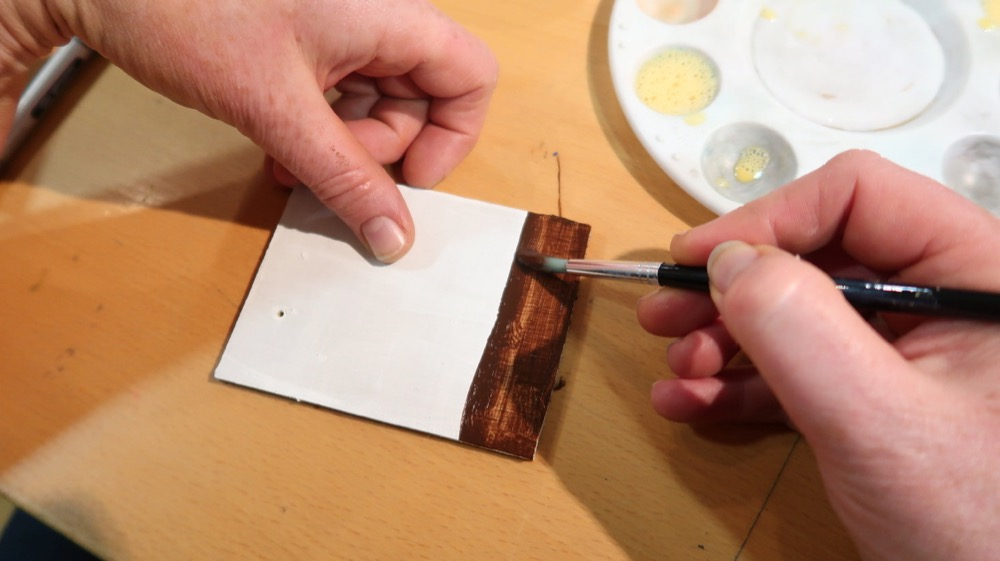 Using the egg to bind the pigment to a pre-prepared plywood piece