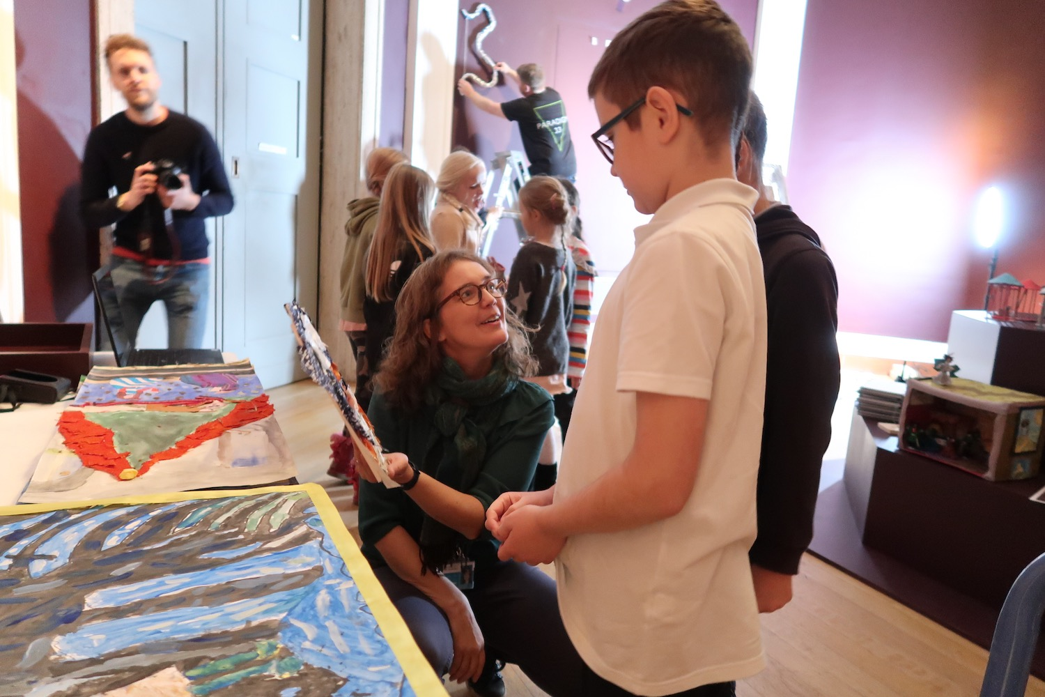 Kate Noble shows children other children's artwork in the Octagon Gallery