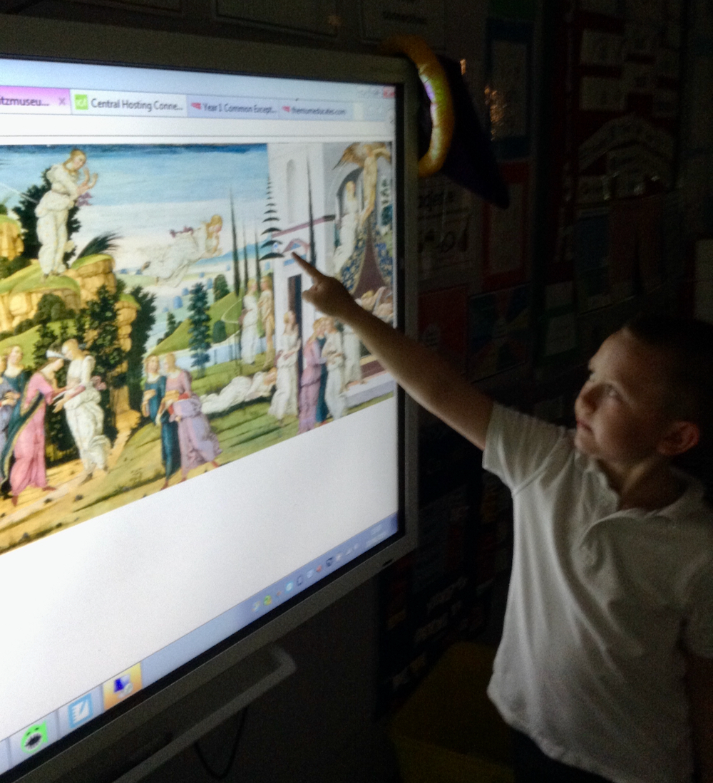 A boy looking at a painting of Cupid and Psyche on a whiteboard in a classroom