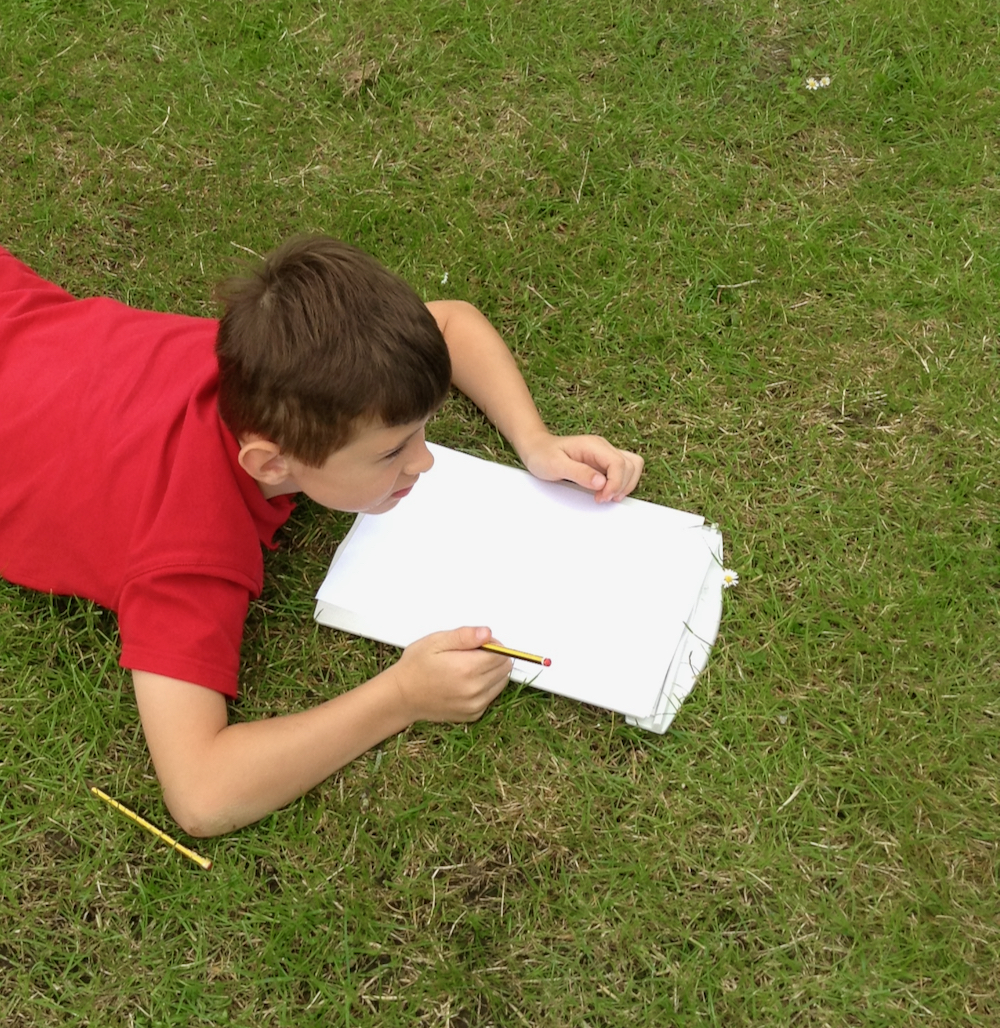 Year Two boy from Hauxton Primary School sitting on grass completing worksheets about trees for Inspire with teacher Pamala Stewart