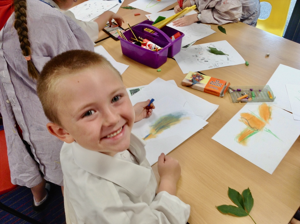Year One boy at Hauxton Primary School drawing leaves with pastels with Pamela Stewart for Inspire
