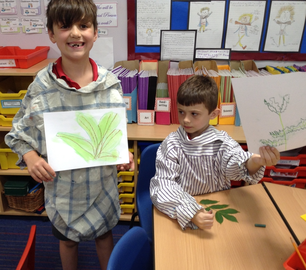 Year Two boy holding up his pastel drawing of a leaf in a year one and two classroom at Hauxton Primary school with teacher Pamela Stewart for Inspire