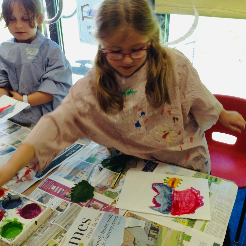 Girl paints a colourful leaf with egg tempera mixing powder paint and egg at Hauxton Primary for Inspire with Pamela Stewart