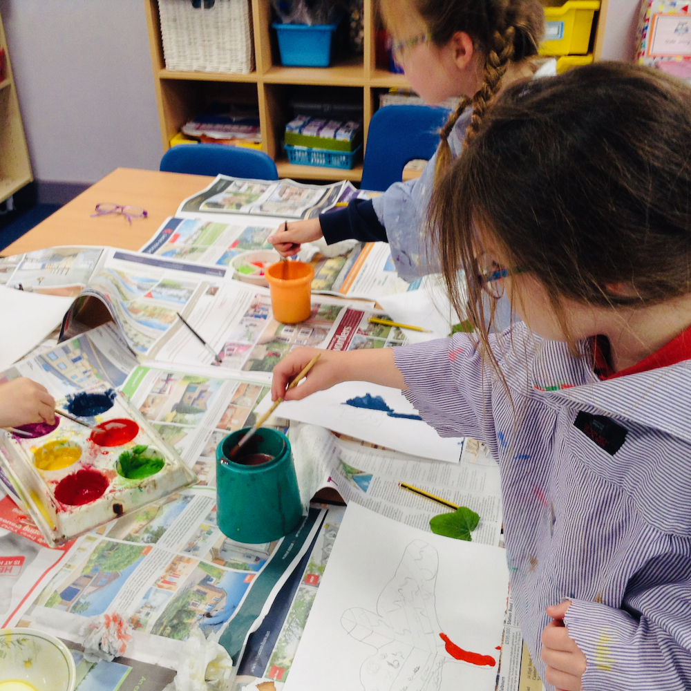 A Year Two girl mixes paints for a colourful leaf with egg tempera mixing powder paint and egg at Hauxton Primary for Inspire with Pamela Stewart